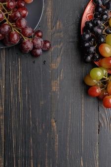 Спелый сочный виноград на тарелку на темное дерево. вид сверху.