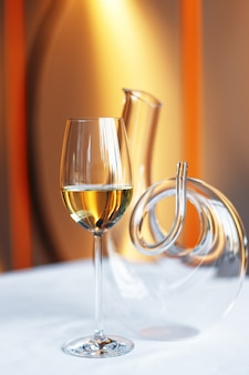 ガラスのワインと白いテーブルクロスをかけたテーブルのデカンター。