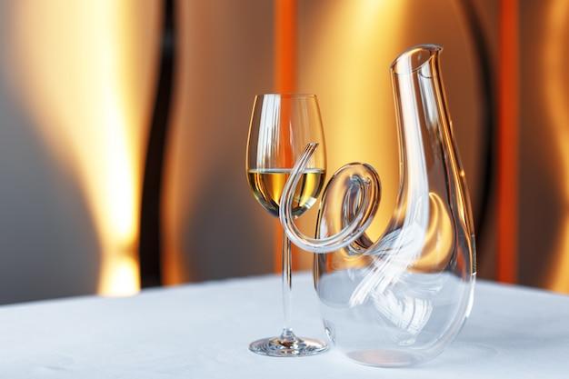 Бокал вина и графин на столе с белой скатертью.