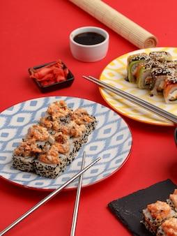 赤の背景に色付きのプレートに巻き寿司