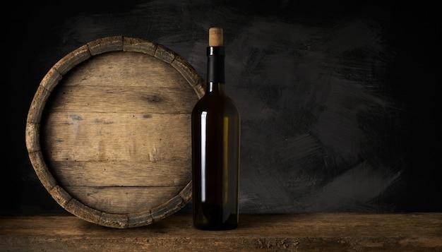 コルク抜きで赤ワインのボトル。黒い木製の背景に。