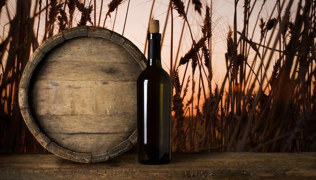 小麦の背景に赤ワインのボトル