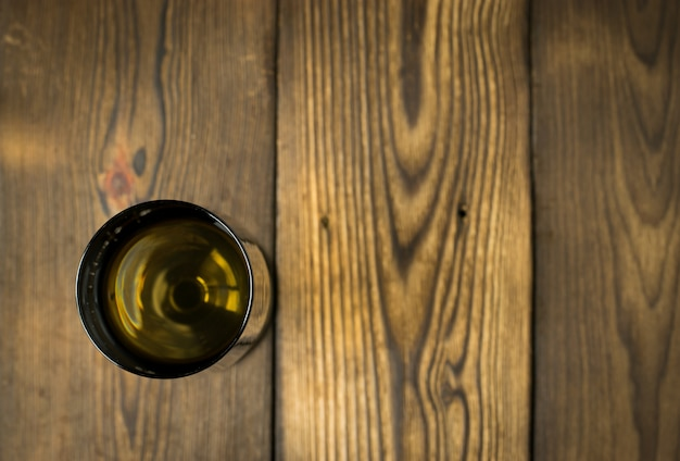 Стекло белого вина на деревянном столе. вид сверху