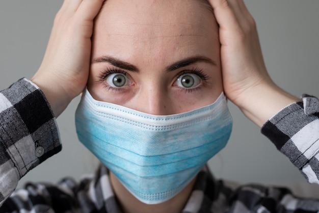Девушка с медицинской маской, чтобы защитить ее от вируса. пандемия коронавируса. женщина с маской стоя. людей, которых госпитализируют, ставят диагноз, часто помещают в карантин (изолятор), чтобы остановить распространение короны.