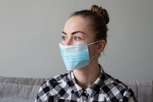ウイルスから彼女を保護するための医療用マスクを持つ少女