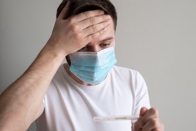 医療マスクを着用し、温度計を保持している男
