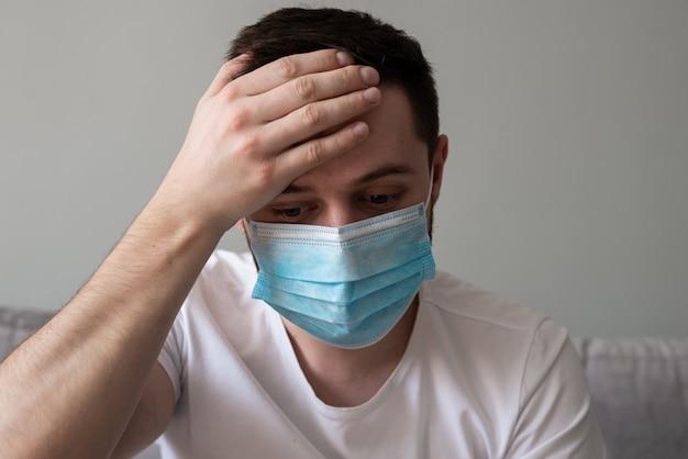 彼の額に彼の手を握ってフェイスマスクを着た男