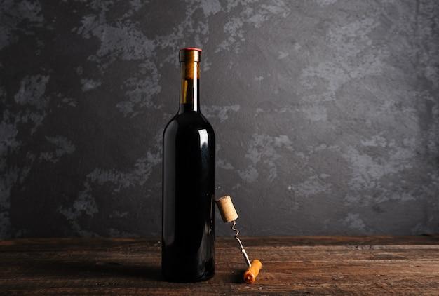 木製の背景に赤ワインの瓶