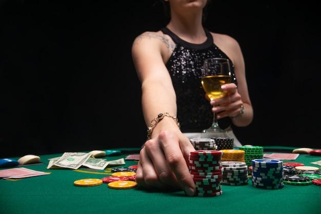 女の子はポーカーをプレーし、チップでベットを上げる