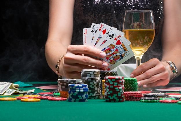 Девушка в казино играет в покер, показывает выигрышные карты