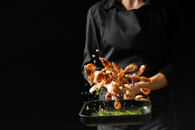 Профессиональный шеф-повар приготовил креветки. кулинарные морепродукты и еда на темном фоне.
