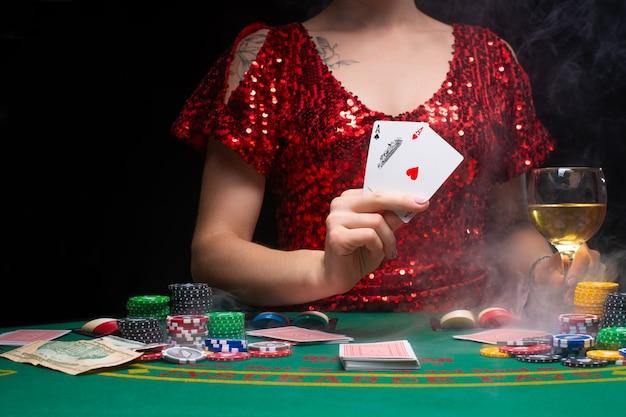 Девушка в вечернем красном платье играет в казино