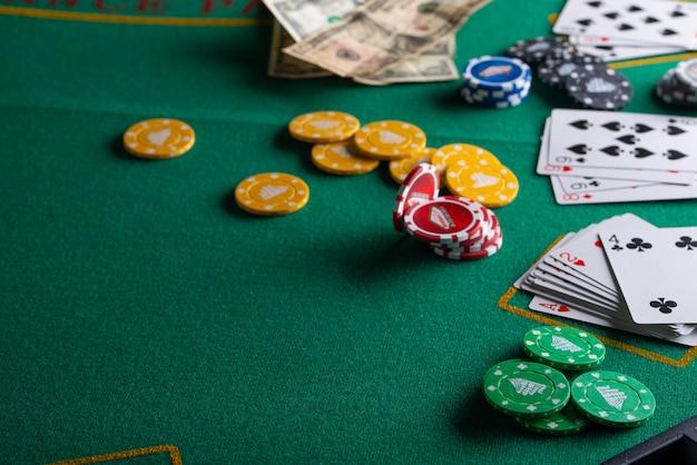 Чипсы, карты и доллары на зеленом столе