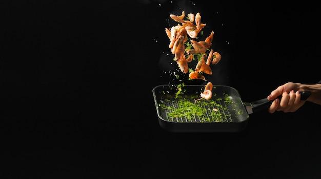 プロのシェフがエビを調理しました。料理用のシーフードと暗い背景の上に食べ物。