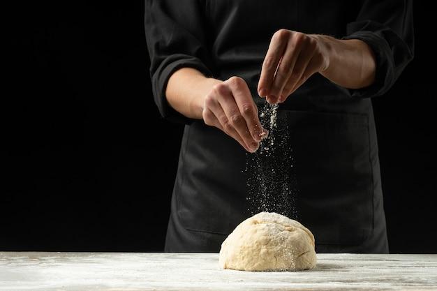 黒い背景に黒いエプロンのシェフが黒い背景にイタリアのピザ、パンまたはパスタを準備します。