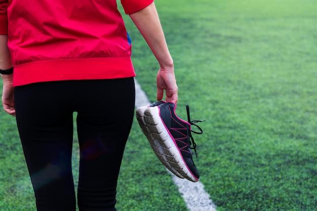 スポーツウェアの女の子はスタジアムを通って歩き、彼女の手でスニーカーを握ります