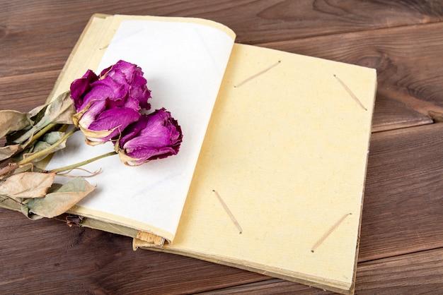 Винтажный фотоальбом на древесине с сухими цветками.