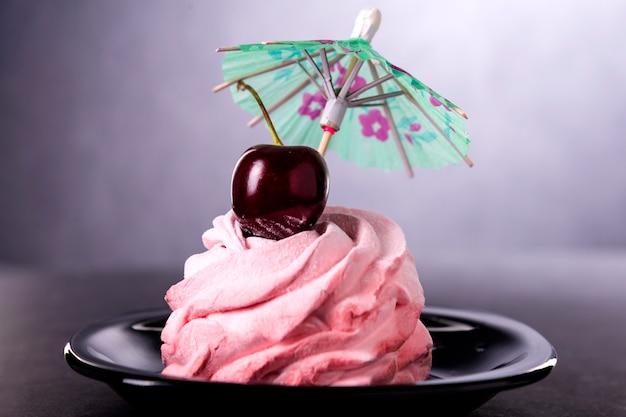 Сладкий розовый торт с одной вишенкой сверху и зонтиком в черном блюдце