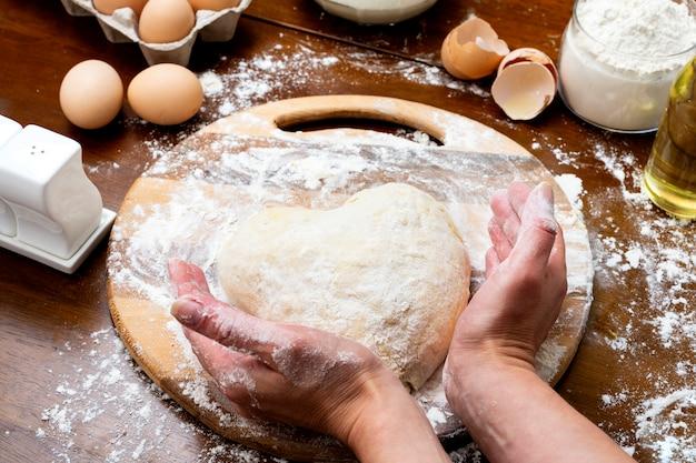 卵と牛乳から生地を作る。ハート型の女性と子供の手で生地。料理とホームコンセプト