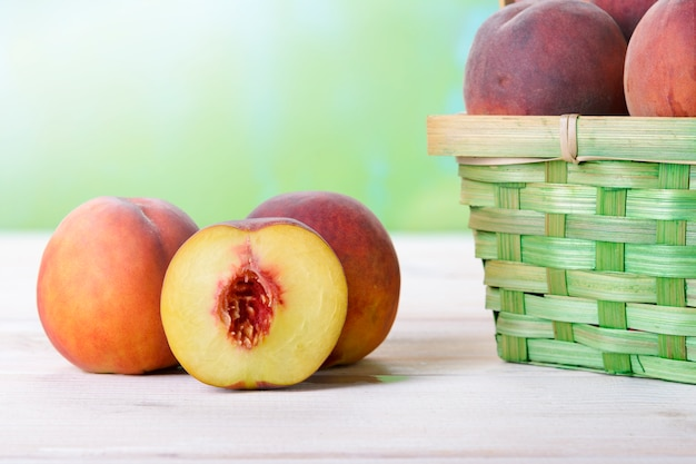 バスケットの横にある木製のテーブルに新鮮な桃
