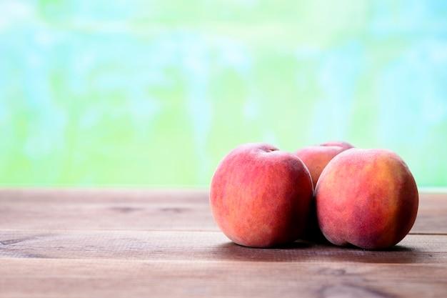 Свежие персики на деревянном столе рядом с корзиной