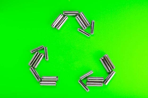 緑の背景にリサイクルの形で電池。バッテリーのリサイクル、環境。