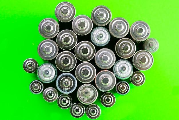 緑の背景のバッテリー。バッテリーのリサイクル、環境。