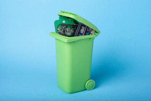 Электронные компоненты в зеленой корзине для отходов
