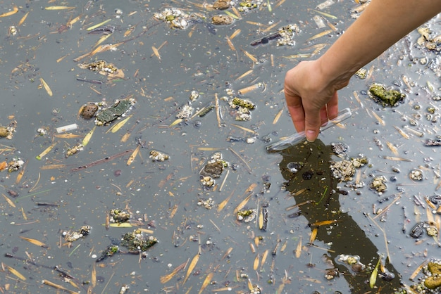 排水中の水の質を確認します。サンプルを手に持つ試験管。下水処理