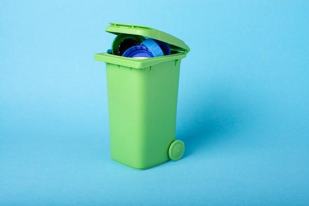 Зеленый мусорный ящик на синем фоне с пластиковыми отходами. переработка пластмасс.