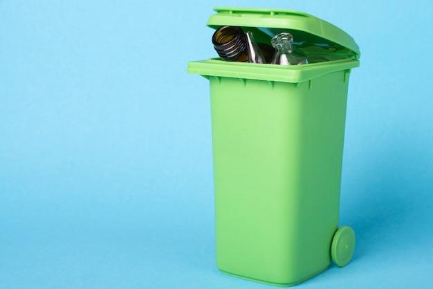 Зеленая мусорная корзина на голубой предпосылке с ненужным стеклом. переработка отходов. экологическая концепция.