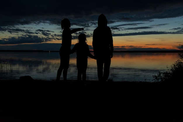 湖で夕日を見ている母親と子供たちのシルエット。家族の概念