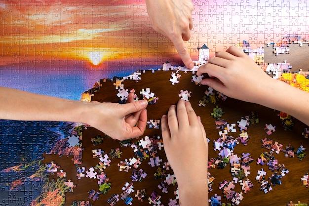 子供と大人の手が木製のテーブルに色のパズルを積み重ねる