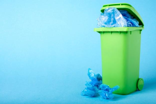 Зеленый мусорный ящик на синем фоне. полиэтилен. переработка отходов.