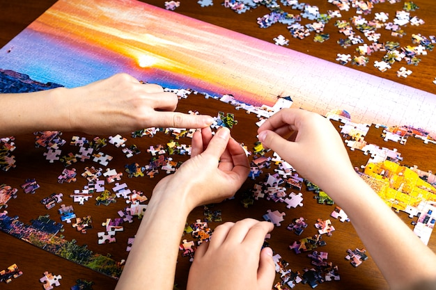 Руки детей и взрослых укладывают цветную головоломку на деревянный стол