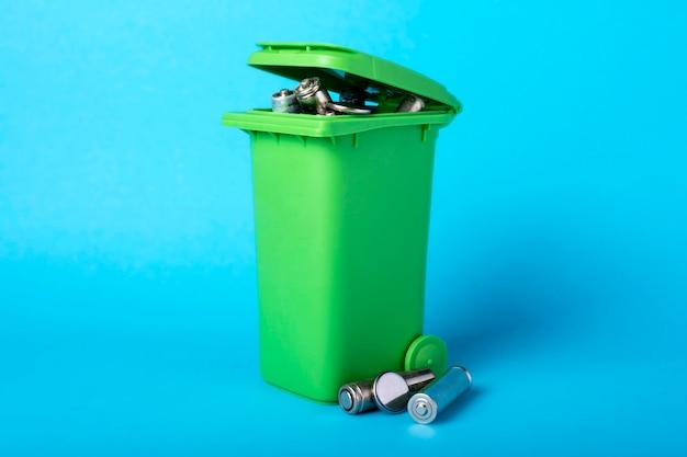 Мусорная корзина на синем. аккумуляторы, аккумуляторы. переработка отходов. экологический