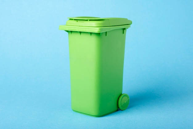 Зеленый мусорный ящик на синем фоне. переработка отходов.