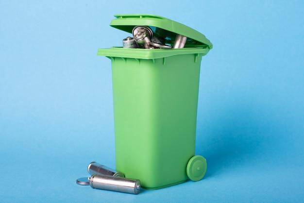Зеленая мусорная корзина на голубой предпосылке с ненужными батареями. переработка отходов. экологическая концепция.