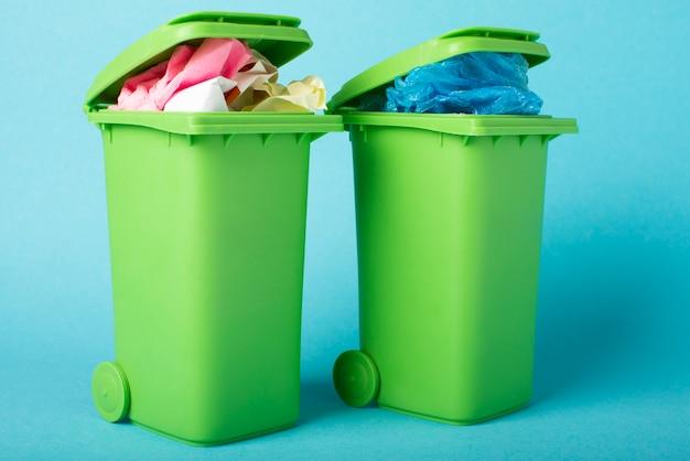Мусорные корзины на синем фоне. бумага и полиэтилен. переработка отходов