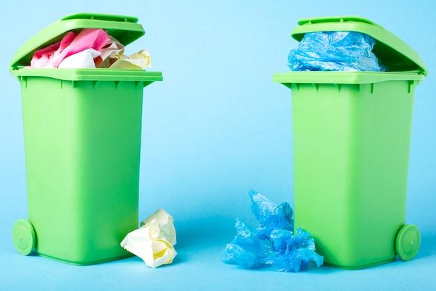 Мусорные корзины на синем фоне. пластиковые. бумага. переработка отходов. экологическая концепция.