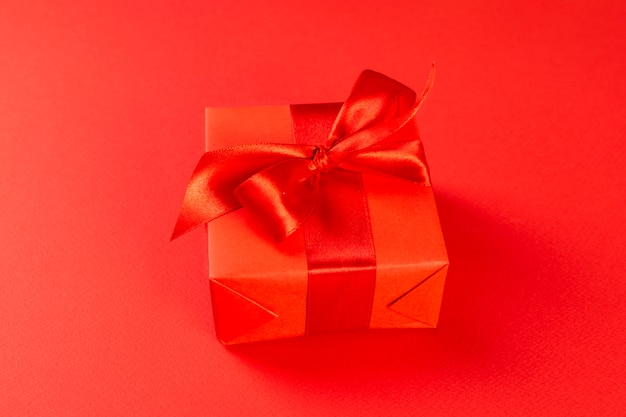 Красная подарочная коробка с красной лентой на красном фоне