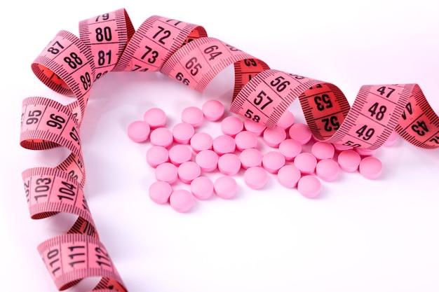 ダイエット薬業界を表す測定テープ付きの薬