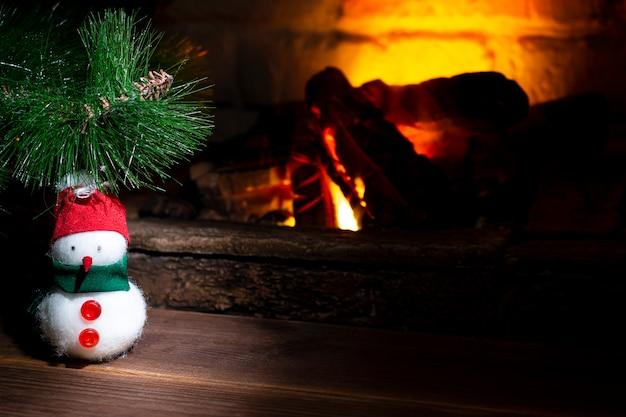 燃える暖炉の近くのクリスマスツリーの下の雪だるま。閉じる。
