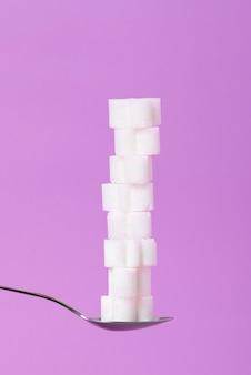 タワーの形で薄紫色の背景に砂糖の部分とスプーン