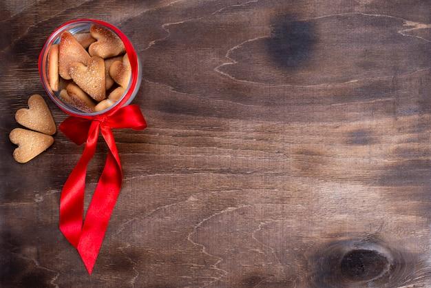 ハート型の茶色の木製テーブルの上の赤い弓と瓶にホリデークッキー。