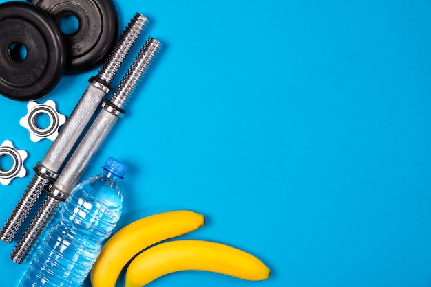 Фитнес или бодибилдинг. спортивный инвентарь, банан, бутылка с водой, штанга, гантель, вид сверху