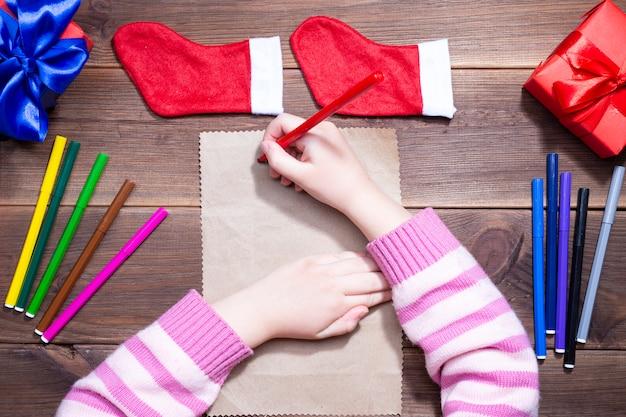 サンタクロースへの子供の手紙。小さな女の子は、クリスマスプレゼントと古い紙の上のクリスマスの装飾と木製のテーブルにマルチカラーのフェルトペンで手紙を書く