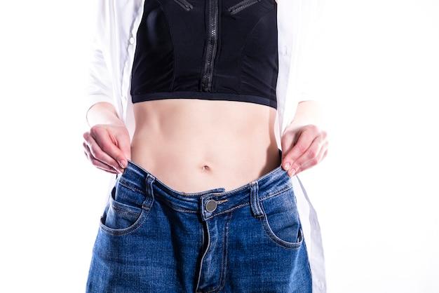 Женщина показывает, сколько веса она потеряла. концепция здорового образа жизни
