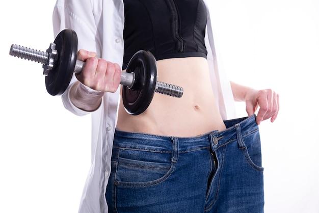 Женщина с гантелей в руке показывает, сколько веса она потеряла. концепция здорового образа жизни и спорта