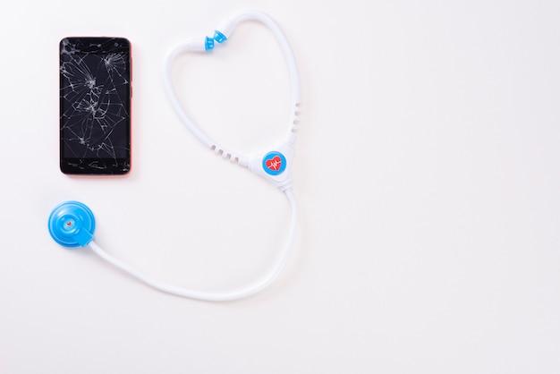 Современный мобильный смартфон со сломанным экраном с детским фанендоскопом, изолированным на белом фоне. вид сверху